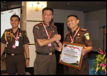 Rizky Rahmatullah (kanan) pada saat menerima penghargaan dari Kajati Kepri, Edy Birton (kiri), foto : ist
