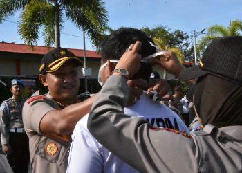 Kompol Agung Gima Sunarya (AGS) pada saat memasangkan masker kepada personil Polres Tanjungpinang.