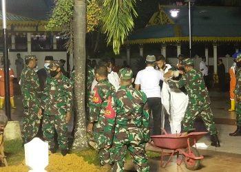 petugas pemakaman Ayah Syahrul sedang menyiapkan Alat Pelindung Diri (APD) lengkap. Foto : mdj/detak.media