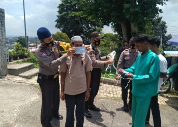 Personil Polsek Batu Ampar pada saat memasangkan masker kepada salah seorang jamaah, f : ist